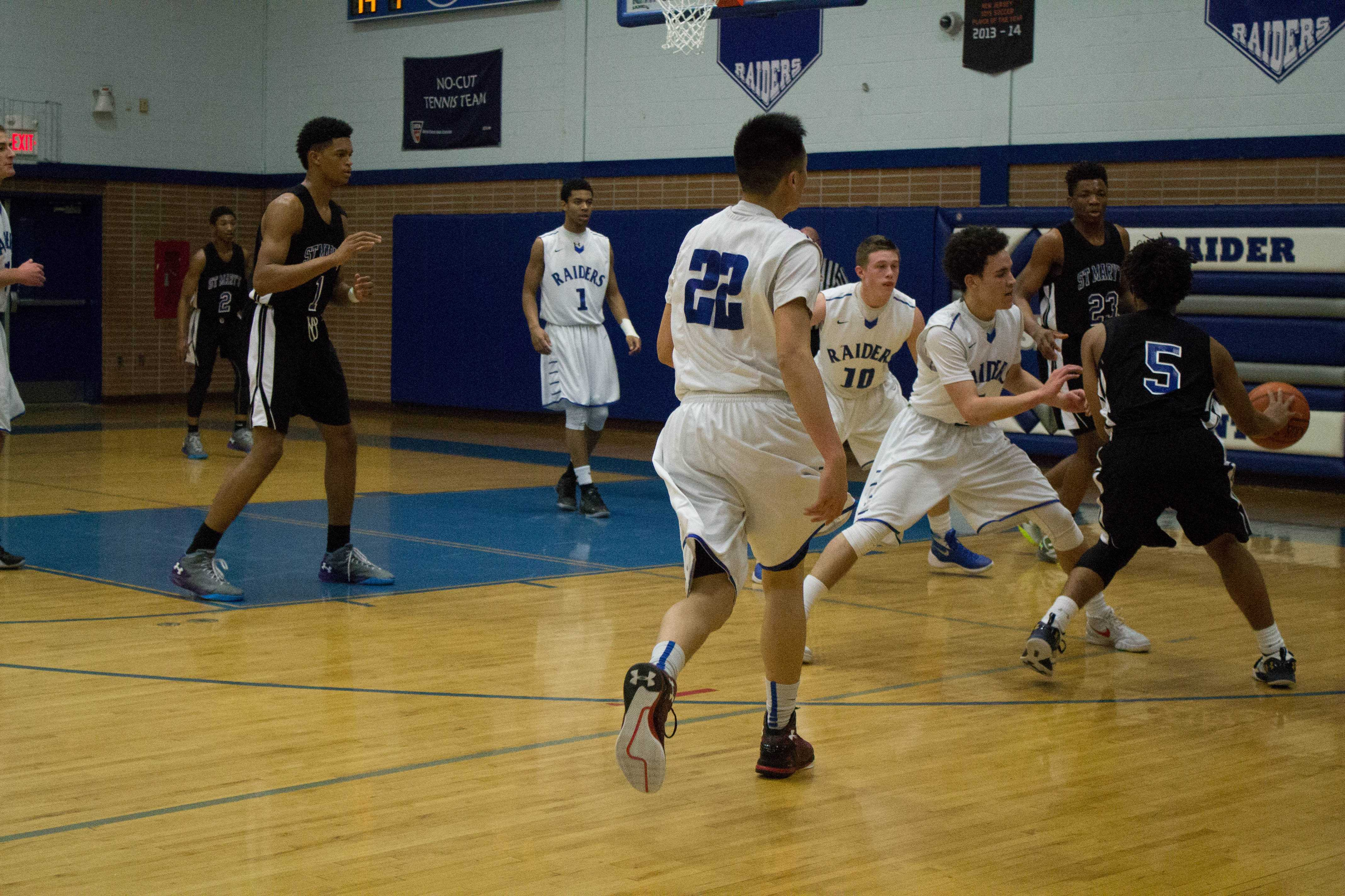 Shooting guard, Theodore Willmott attempts to steal the ball away from St. Mary.