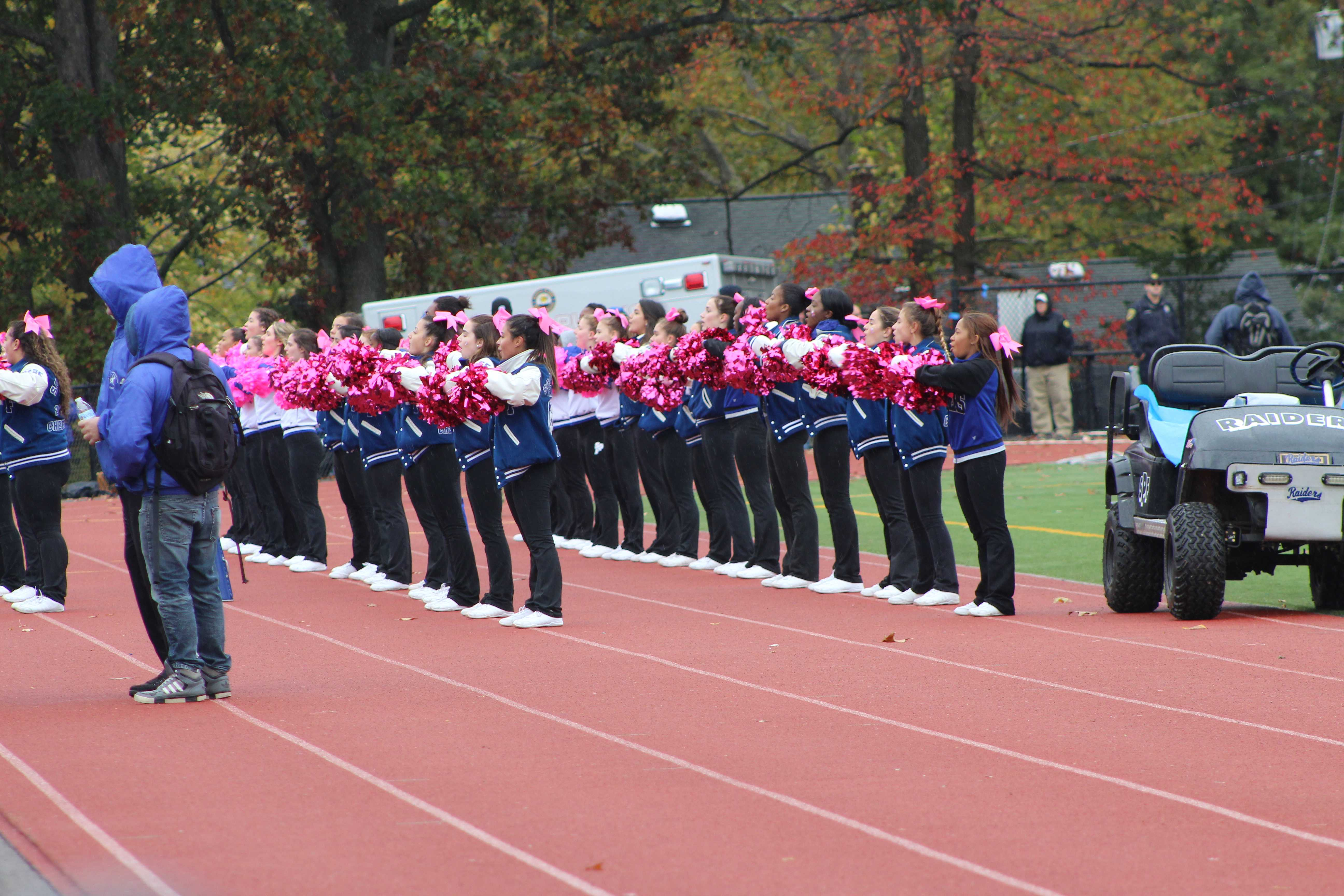 The varsity cheer team are cheering for the Raiders. The squad were trying to hype the audience to support the raiders.
